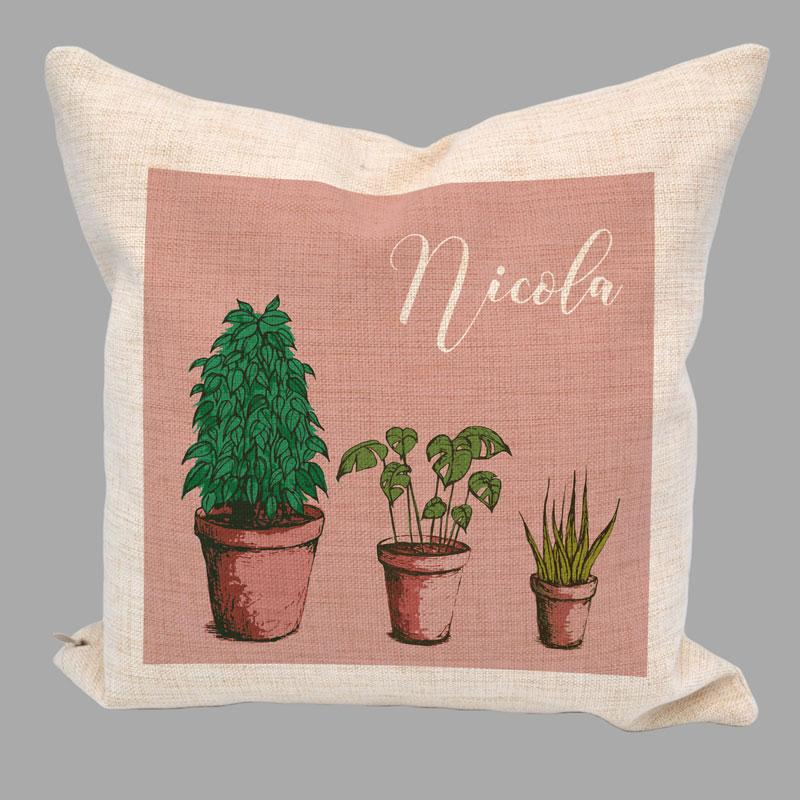 Personalised linen cushion with a leafy houseplant pattern and the name Nicola printed on it