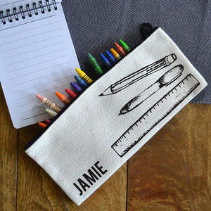 A personalised linen pencil case with a black line drawing of a pen, pencil and ruler and the name Jamie in black lettering.