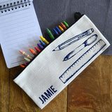 A personalised linen pencil case with a navy blue line drawing of a pen, pencil and ruler and the name Jamie in navy blue lettering.