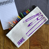 A personalised linen pencil case with a purple line drawing of a pen, pencil and ruler and the name Jamie in purple lettering.