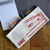 A personalised linen pencil case with a red line drawing of a pen, pencil and ruler and the name Jamie in red lettering.