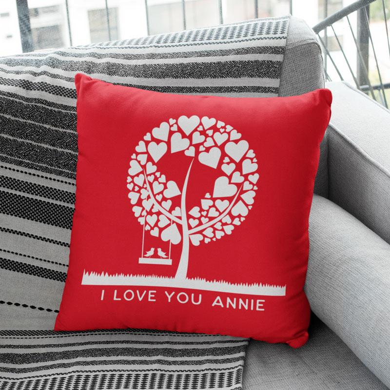 A personalised red Valentine's day cushion with a white tree printed on it