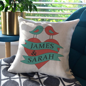 A personalised linen cushion with a love birds design printed on it in pink and blue