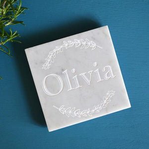 "A personalised engraved white marble coaster with the name ""Olivia"" etched into the surface."