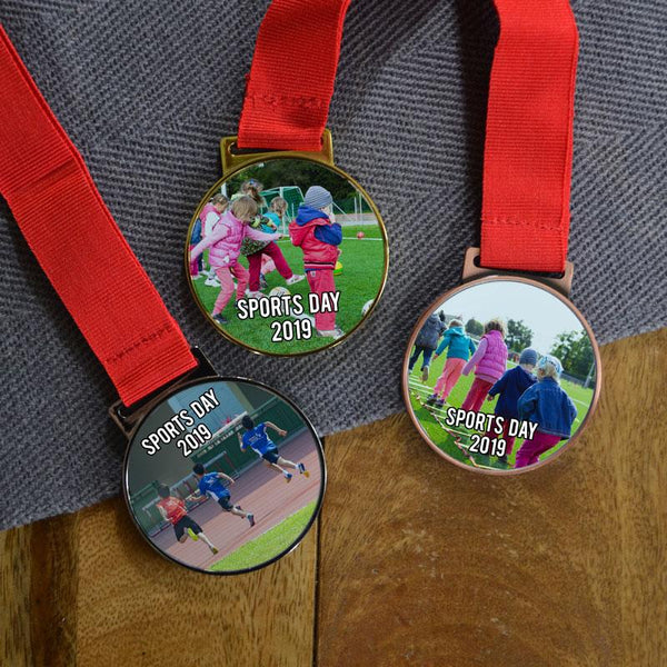 "Three personalised medals for a school sports day. One bronze, one silver and one gold. The medals have sports day photo printed in the centre and the words ""Sports Day 2019"" in white lettering."