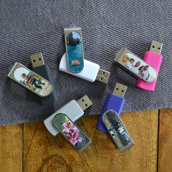 A collection of personalised memory sticks with photos printed on them. The memory sticks are a range of different colours including pink, blue white black and grey.