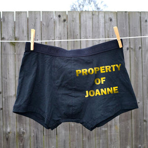 "A personalised pair of black boxer shorts with the words ""Property Of Joanne"" printed in yellow lettering on them."
