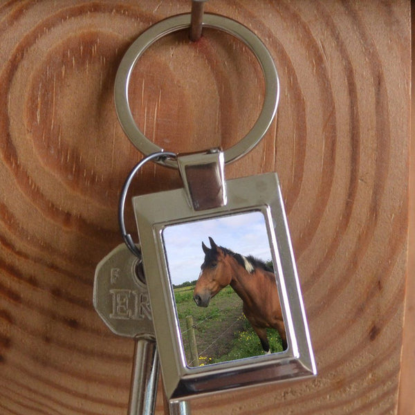 A personalised metal keyring in a rectangular shape. The keyring contains a family photo.