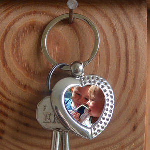 A personalised metal keyring in a heart shape. The keyring contains a family photograph.