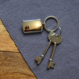 Personalised metal keyring on a table. The keyring is personalised with a photo of people looking at a sunset.