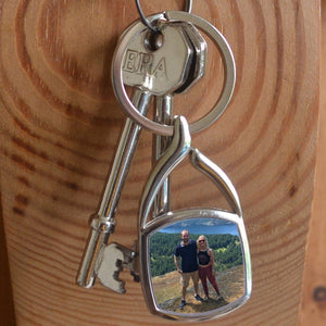 A personalised metal keyring in a square shape containing a holiday photo