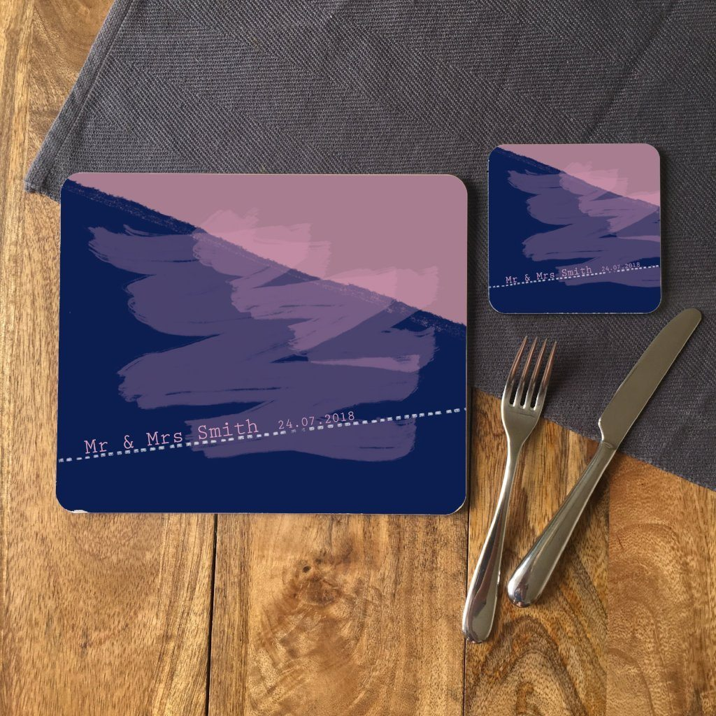 "A personalised rectangular placemat and a square coaster with matching designs. The design is an abstract pattern in pink and blue. The design includes text which reads ""Mr and Mrs Smith, 24/07/2018"""