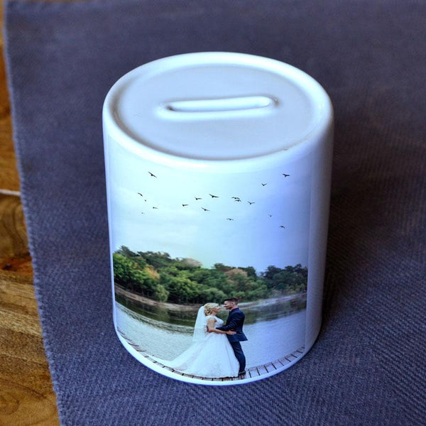 A personalised money box in white with a photo from a wedding printed on it