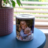 A personalised photo money box on a blue table