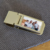 A personalised shinny metal money clip with a family photo printed on it.