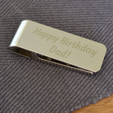A personalised shinny metal money clip with a birthday message printed on it.