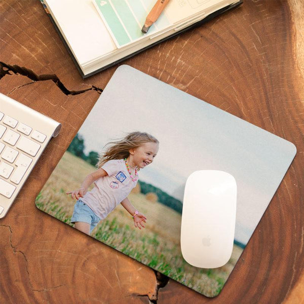 A personalised photo mouse mat with a photograph of a child printed on it