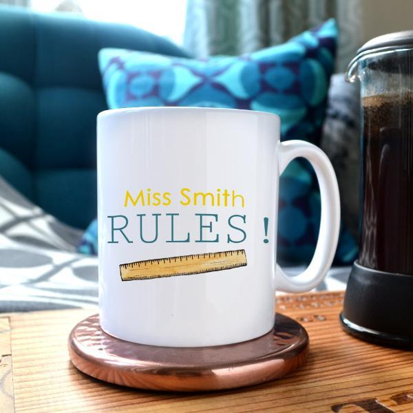 "A personalised mug on a copper coaster next to a pot of coffee. The design includes text which reads ""Miss Smith rules"" and an illustration of a ruler."