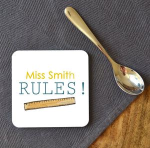 A square coaster personalised with a teachers name. The design includes yellow and blue text with a ruler underneath.