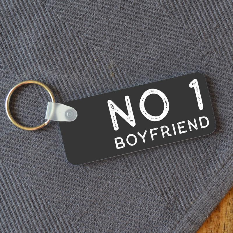 "A personalised rectangular keyring with the words ""No 1 Boyfriend"" in white lettering on a charcoal grey background"