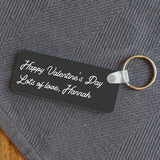 "A personalised rectangular keyring with the words ""Happy Valentine's Day. Lots of love, Hannah"" in white lettering on a charcoal grey background"