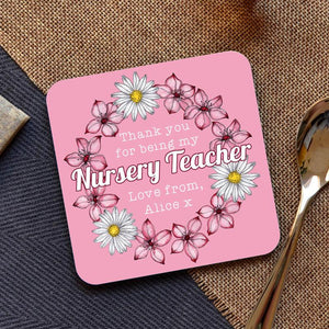 "A personalised pink coaster with a flower pattern and the words ""thank you for being my nursery teacher love from Alice"" printed on it."