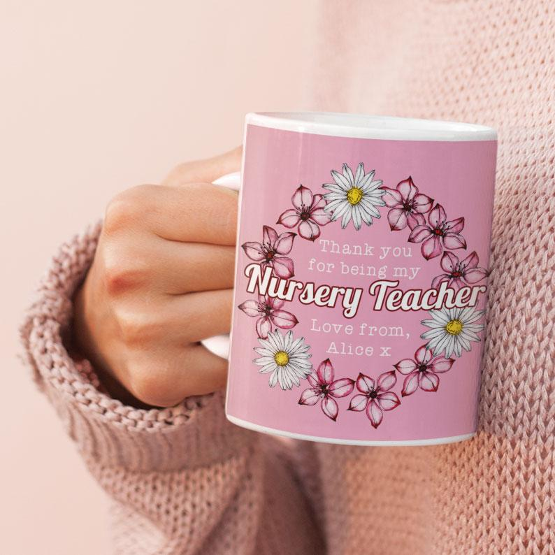 "A personalised pink mug with a flower pattern and the words ""thank you for being my nursery teacher love from Alice"" printed on it."