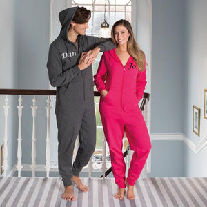 Personalised printed adult onesies, a man is wearing a grey one and a woman is wearing a hot pink one