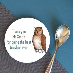 "A round coaster next to a teaspoon. The coaster has a design which features an illustration of an owl and the message ""thank you mr smith for being the best teacher ever"""
