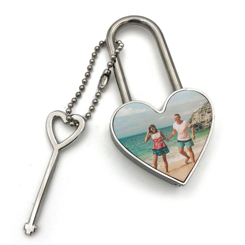 A meatal heart shaped padlock with a photo of a couple on a beach on the front and a heart shaped key.