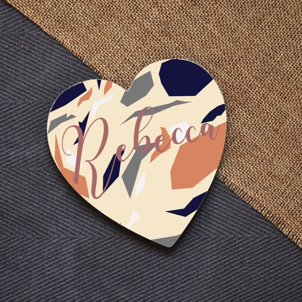 A personalised terrazzo patterned heart coaster, the coaster is personalised with the name Rebecca