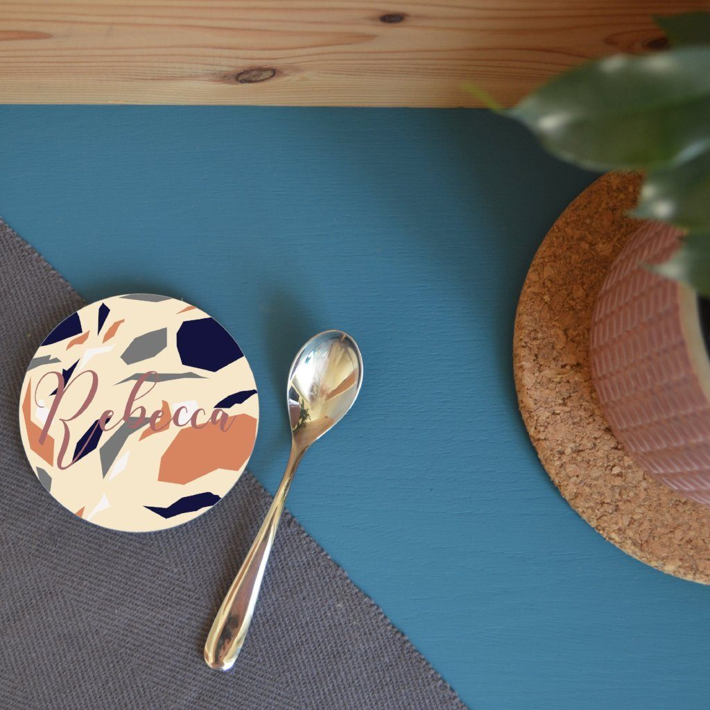 A personalised round terrazzo coaster on a table next to a house plant