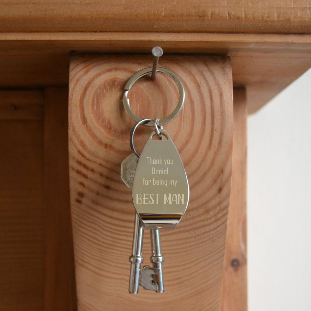 A personalised bottle opener keyring hanging on a hook with 2 keys