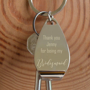 "A personalised metal bottle opener keyring with 2 keys attached. The keyring has an engraved message which reads ""Thank you Jenny for being my bridesmaid"""