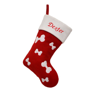 "A personalised Christmas stocking for a dog. The stocking is red with a pattern of white dog bones. The name ""Dexter"" is embroidered in red on the white top section of the stocking."