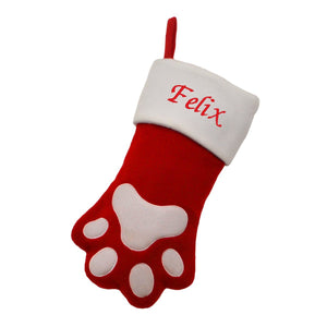 "A personalised Christmas stocking for an animal, the stocking is in the shape of a dog or cat paw. The stocking is red and white with the name ""Felix"" embroidered on the white top section."