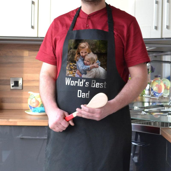 "A personalised black apron with a photo of 2 children printed on it and the words ""World's Best Dad"""