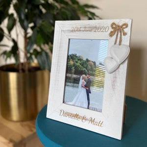 A personalised white wooden photo frame with 2 decorative wooden hearts and an engraved message.