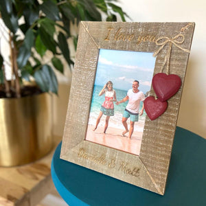 A personalised wooden photo frame made from rustic brown wood. The frame has a messaged engraved on the top and bottom.