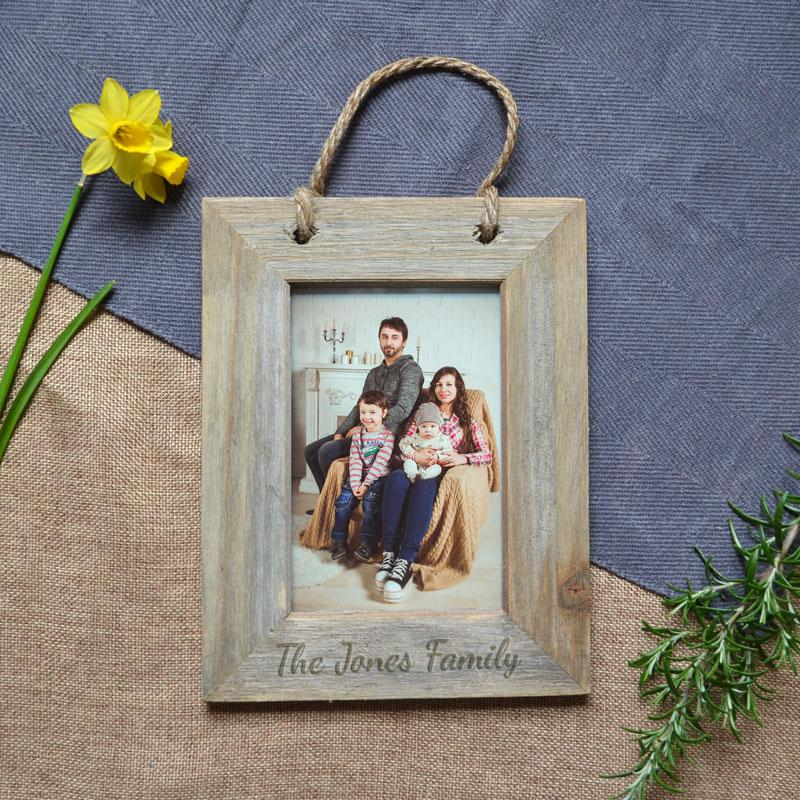 "A personalised wooden photo frame with a family photo inside. The frame has the words ""the Jones family"" engraved into the wood underneath the photo."