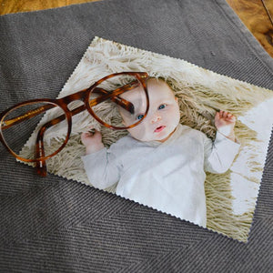 A personalised lens cloth with a photo of a baby printed on it