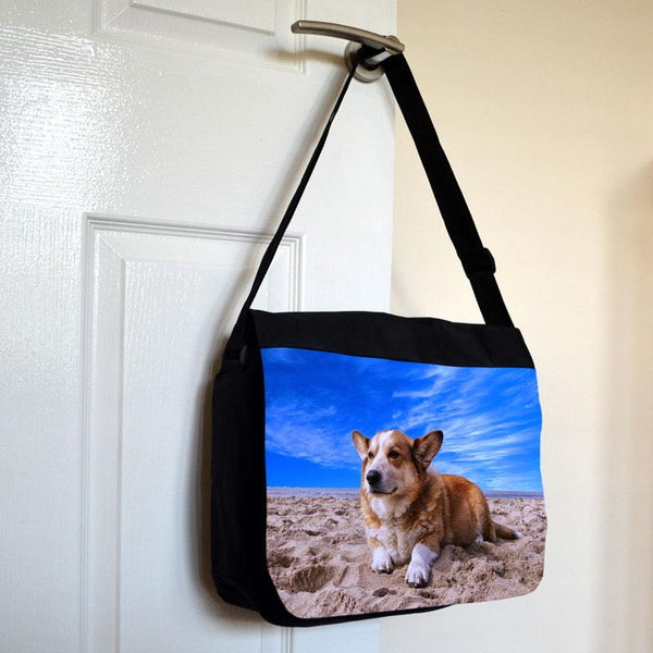 A black messenger bag with a photo printed on the front hanging on a door handle