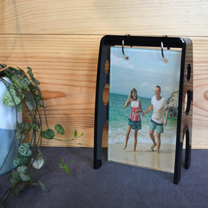 A personalised glass photo tile hanging in a black acrylic frame, the rectangular glass tile is printed with a photo of a couple on holiday.
