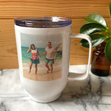 A personalised white metal photo travel mug with a photo of two people on a beach printed on the side.