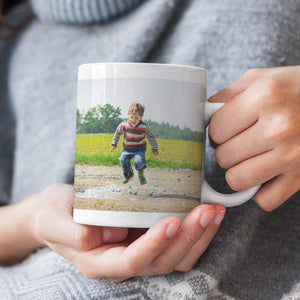A personalised photo mug with a photo of a child jumping in a puddle printed on it