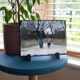 A personalised photo slate on a table by a window. The slate has a photo of a dad and daughter printed on it.