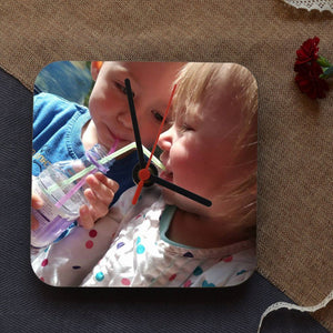 A square clock which is personalised with a photo of 2 children