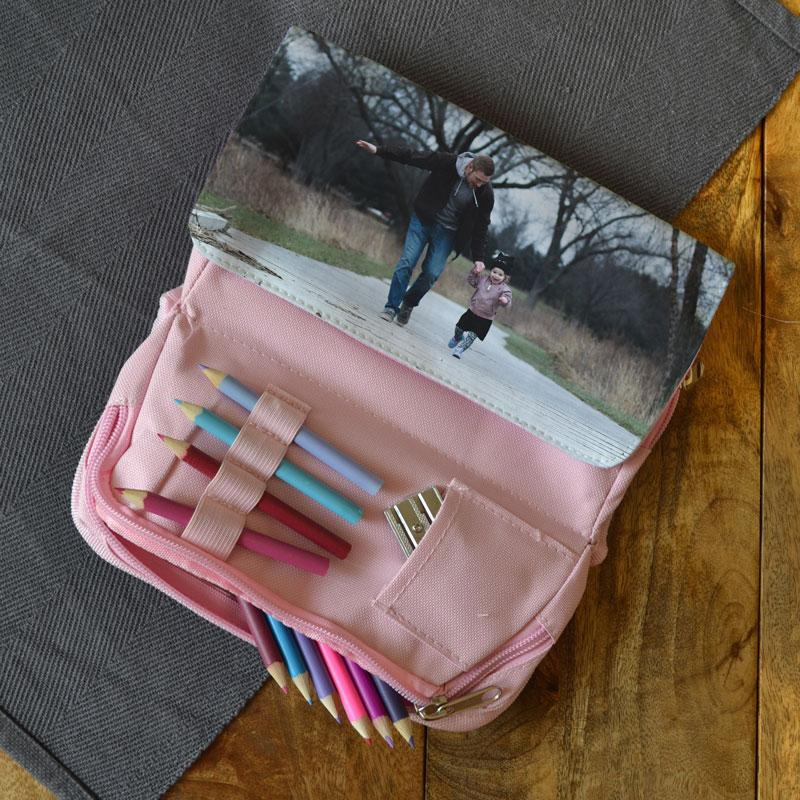 The inside view of the pink pencil case showing the different pockets for storing pens and pencils
