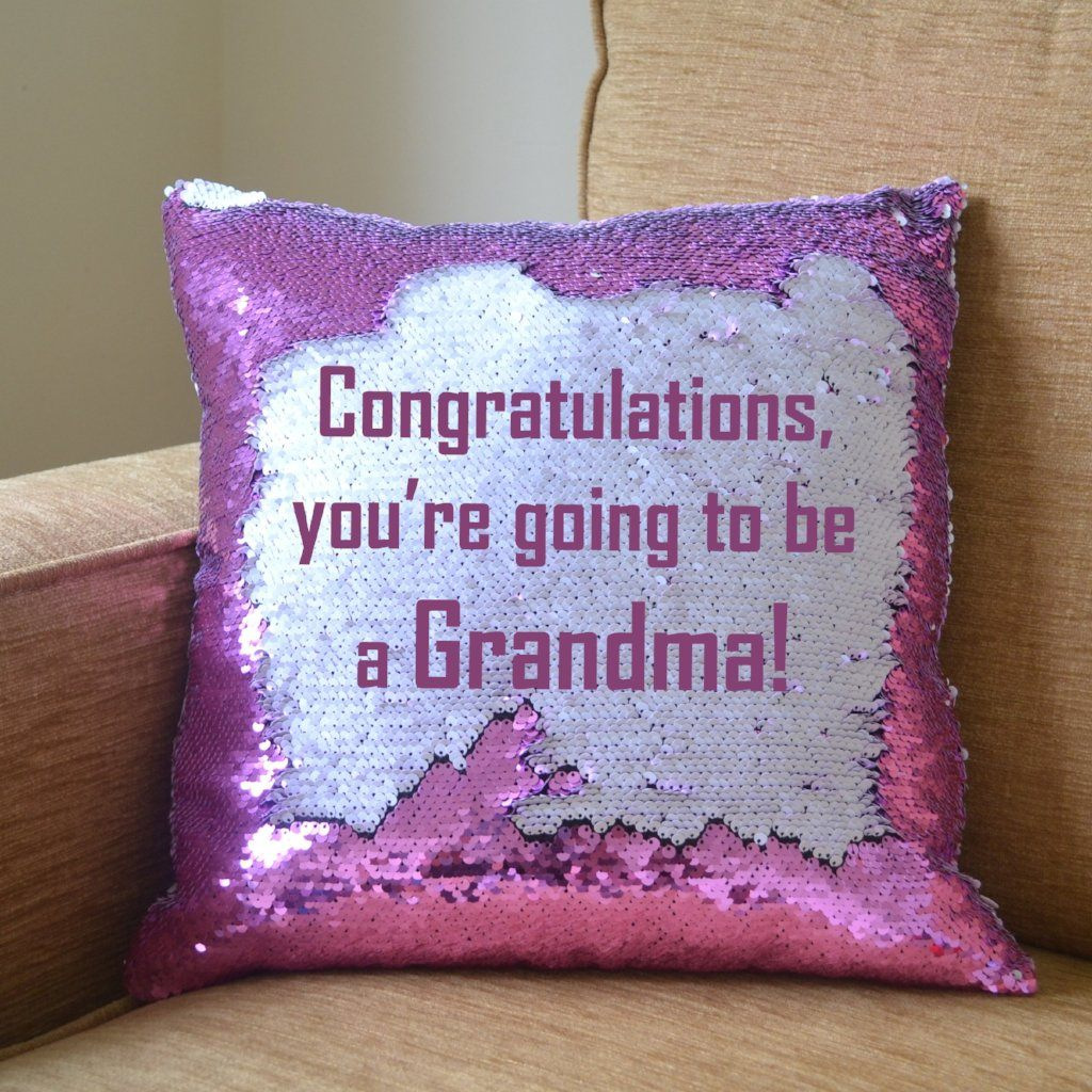"A pink sequin reveal cushion with its hidden message on show, the message reads ""Congratulations, you're going to be a Grandma!"""