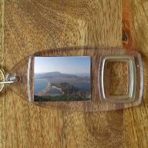 A plastic bottle opener keyring which is personalised with a holiday photo